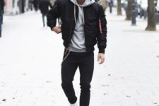 a black bomber jacket, a grey hoodie, black jeans and white trainers for a cold fall or winter day