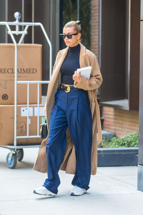 a black crop turtleneck, navy striped overiszed pants, white trainers and a tan coat for a cold day