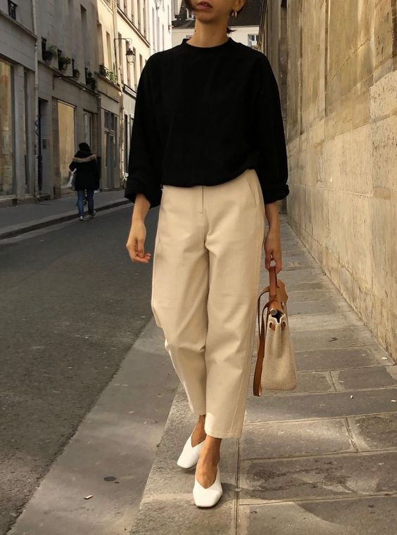 a black jumper, neutral oversized cropped pants, white trendy shoes and a neutral bag to go to work
