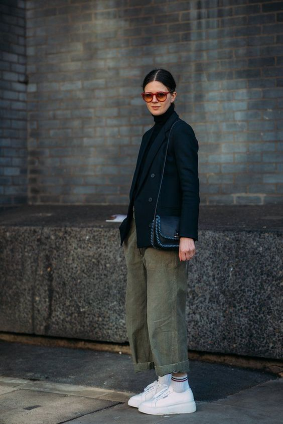 a black turtleneck, a black blazer, green oversized pants, white sneakers and white socks with stripes for the fall
