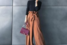 a black turtleneck, rust-colored high waisted wideleg pants, black shoes and a burgundy bag