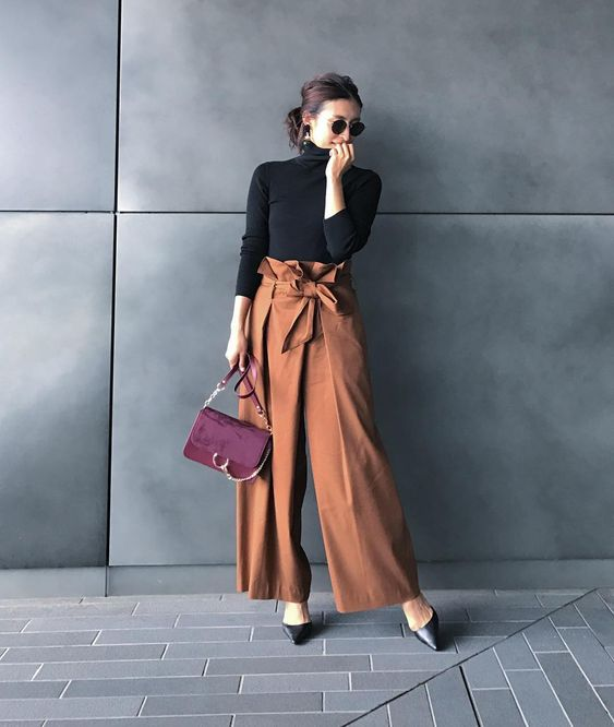 a black turtleneck, rust colored high waisted wideleg pants, black shoes and a burgundy bag