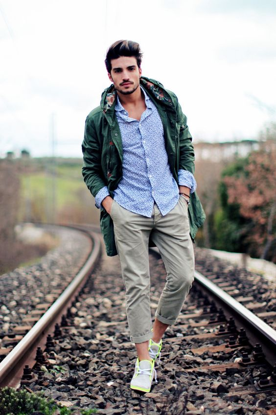 a blue printed shirt, grey pants, grey and neone yellow trainers, a green parka for a bright fall look