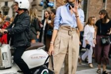 a blue shirt, tan oversized pants, black boots and a graphic bag for a refined fall outfit
