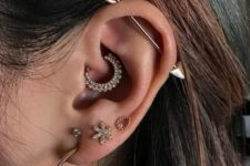 a bold ear with four lobe piercings, a daith piercing and an industrial one with shiny earrings and a bar