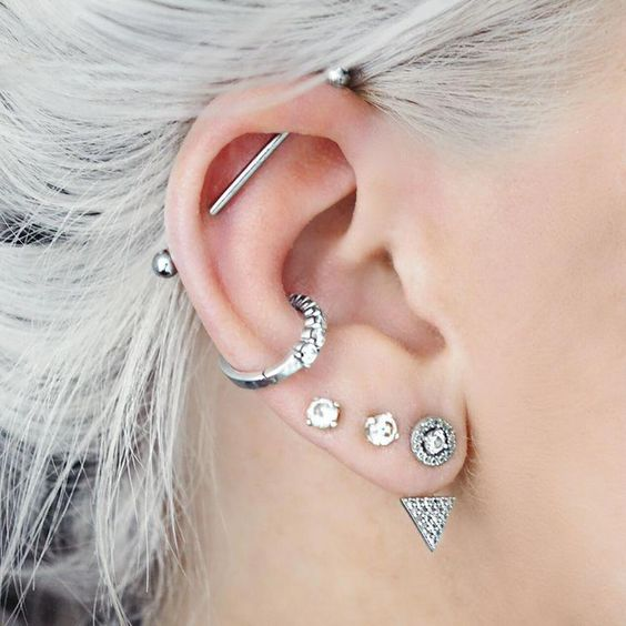 a boldly accessorized ear with three lobe piercings, a hoop in the helix and an industrial bar
