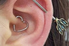 a cool look with a lobe, daith and industrial piercings accessorized with a stud, a heart hoop and an arrow bar