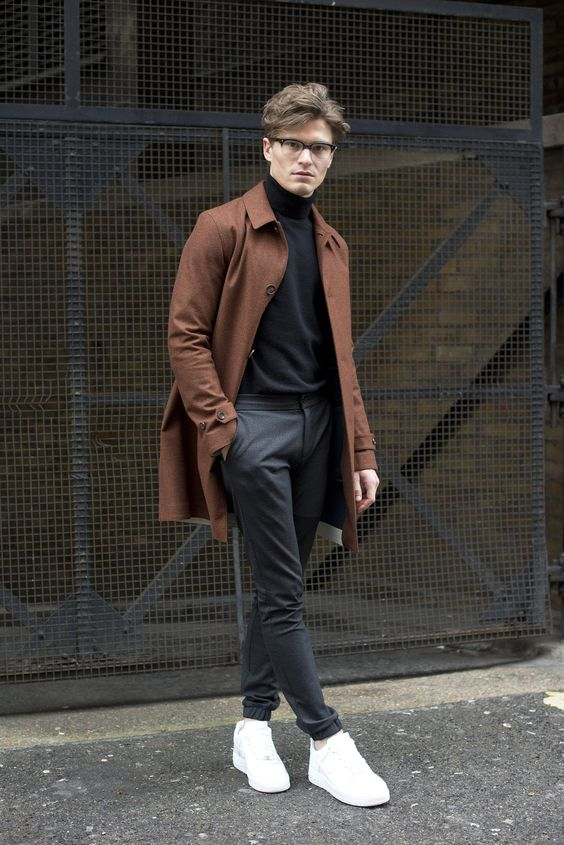 a fall outfit with a black turtleneck, grey joggers, a rust colored coat and white sneakers