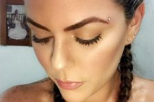 a microdermal piercing over the eyebrow is a delicate and shiny accent to it