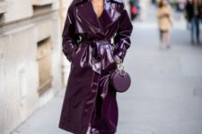a monochromatic look with a purple lacquer leather trench and a matching purple bag plus black shoes with white feathers