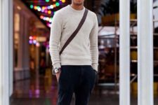a neutral sweater, black pants with pockets, brown shoes and a crossbody bag for much comfort