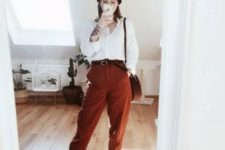 a relaxed outfit with a white shirt, rust oversized pants, orange sneakers and striped socks plus a beanie