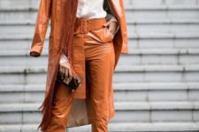 a rust-colroed lacquered leather trench and matching cropped pants, a white shirt and nude heels