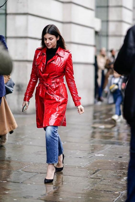 a simple look of a black turtleneck, blue jeans and black heels is elevated with a red lacquered trench