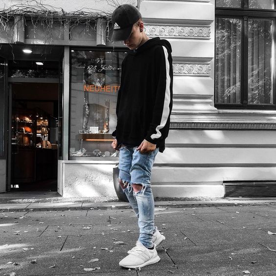 a simple look with a black hoodie, blue ripped jeans, white trainers and a black cap will never go out of style