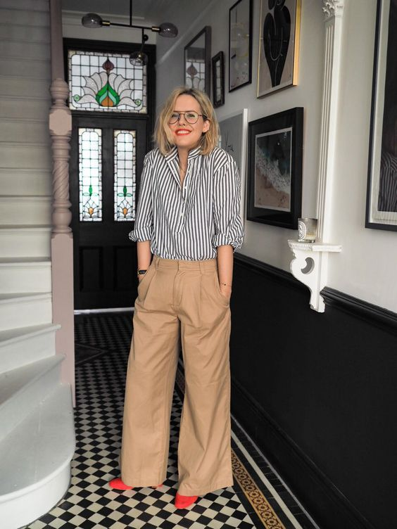 a striped black and white shirt, beige oversized pants, red shoes for a vintage-inspired and chic look