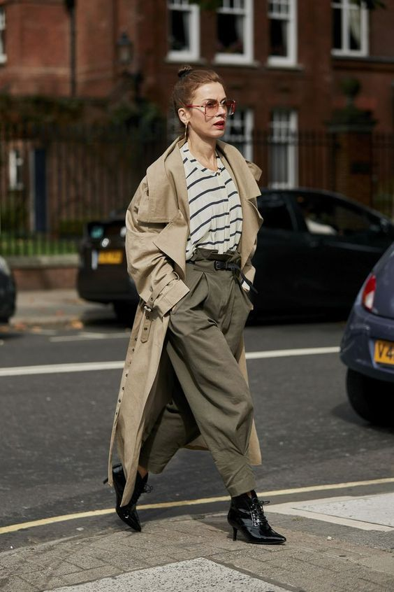 a trendy outfit with a striped oversized tee, dark green oversized pants, black boots and a tan trench