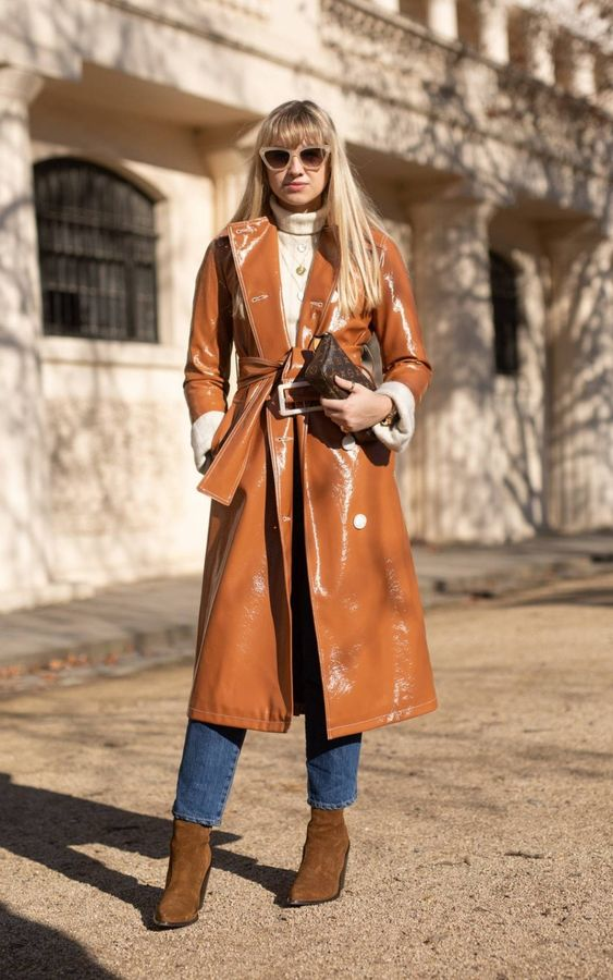 a white sweater, blue cropped jeans, brown suede booties, a rust colored lacquered leather trench