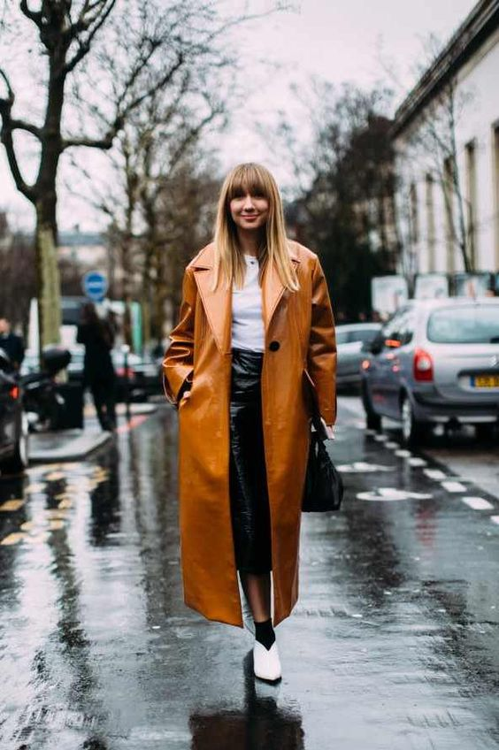 a white tee, a black leather skirt, white booties and black socks plus a rust colored lacquered trench