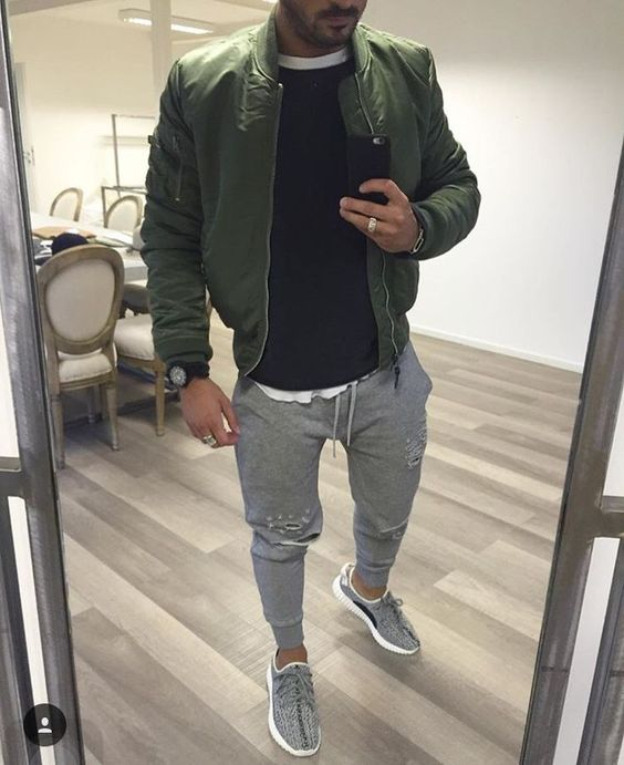 a white tee, a blakc jumper, a green bomber jacket, grey joggers and grey trainers for a sport chic look