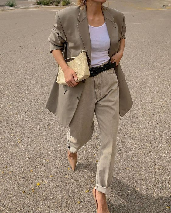 a white top, neutral oversized pants, a taupe oversized blazer, beige shoes and a neutral clutch