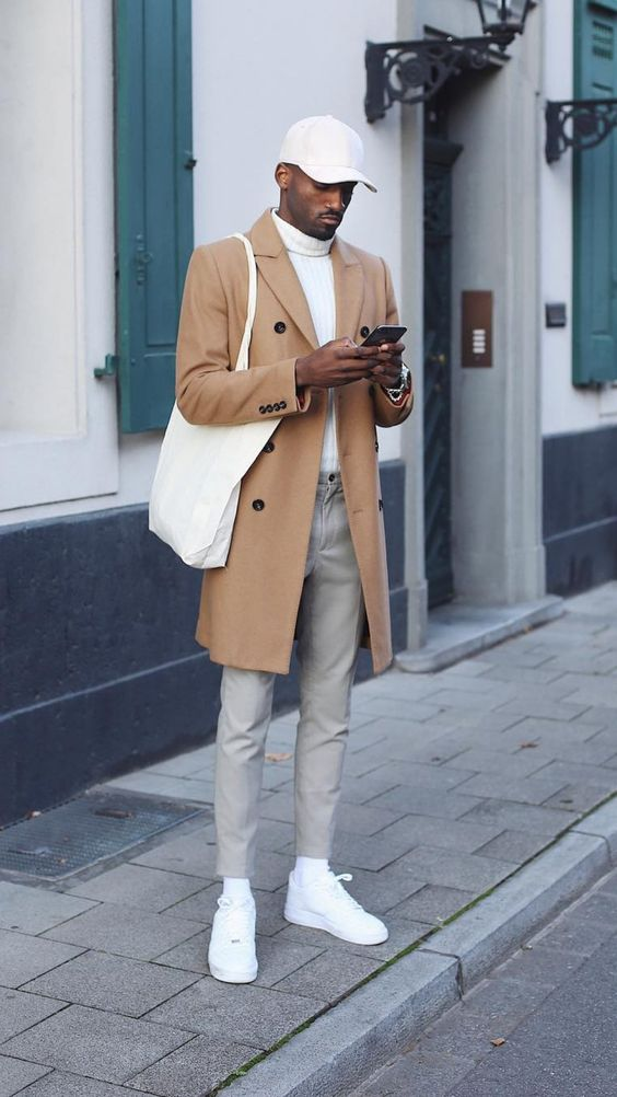 a white turtleneck, grey pants, a camel trench, white sneakers and socks, a cap and a tote