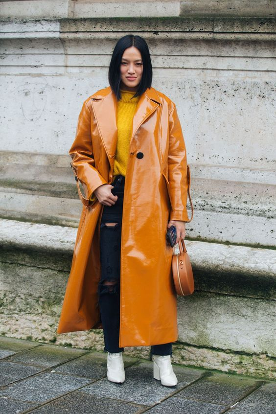 an amber lacquere straight leather trench, black ripped jeans, a mustard turtleneck and white boots