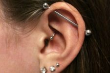 an elegant look with three lobe piercings, a daith one and an industrial one done in silver and with rhinestones