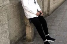 black sporty pants, black trainers, a white denim jacket for a monochromatic fall look