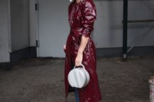 blue jeans with a raw hem, a burgundy lacquered leather trench, silver booties and a matching round bag