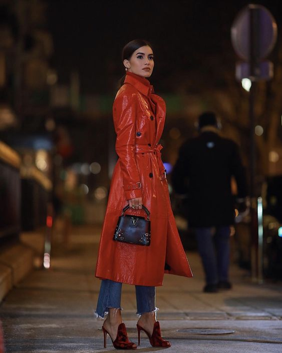 blue jeans with a raw hem, a red lacquered leather coat, red and black mules and a small black bag