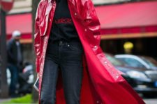 grey cropped jeans, a black hoodie with red letters, black and red boots, a fuchsia lacquered leather trench