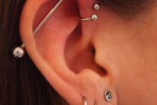 three lobe piercings, a helix one and an industrial one done with the similar accessories