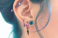 three lobe piercings and a vertical industrial one all done with turquouse and purple earrings and a bar