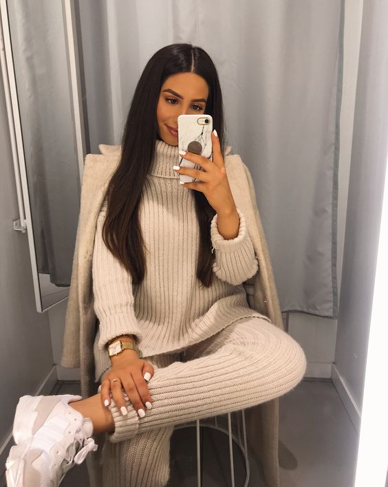 a white knit suit with pants and a turtleneck sweater, white trainers, a creamy coat for a chic touch