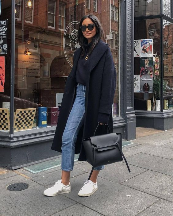 a black turtleneck, blue cropped jeans, white sneakers, an oversized midnight blue coat and a black bag