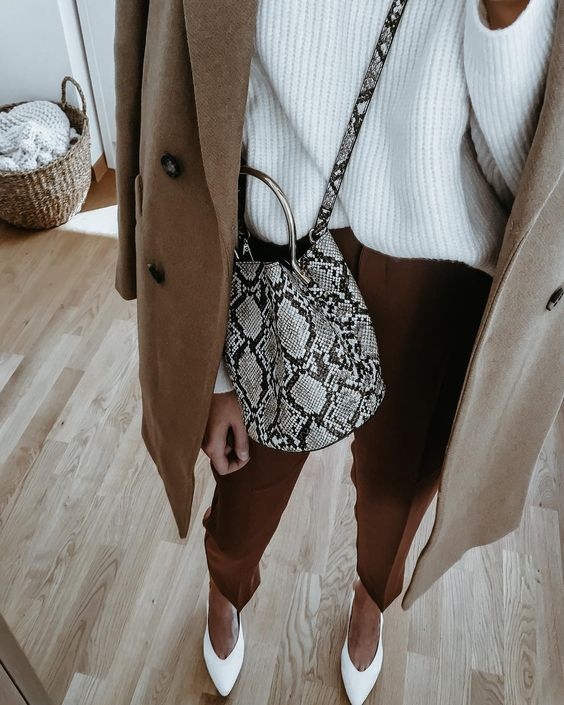 a chic fall look with rust pants, a white oversized sweater, white shoes and a camel coat plus a snake bag