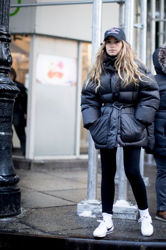 a monochromatic look with black leggings, a black cap, white sneakers and an oversized black padded jacket with a belt