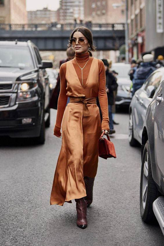 a rust turtleneck, an orange silk slip dress, burgundy boots and an orange suede bag for an ultimate fall look