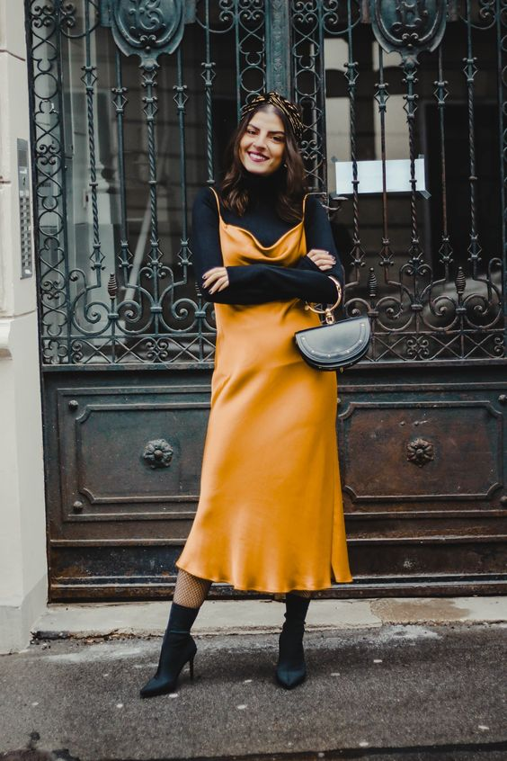 a black turtleneck, a marigold slip midi dress, black sock boots and a black bag with a ring handle for a girlish feel