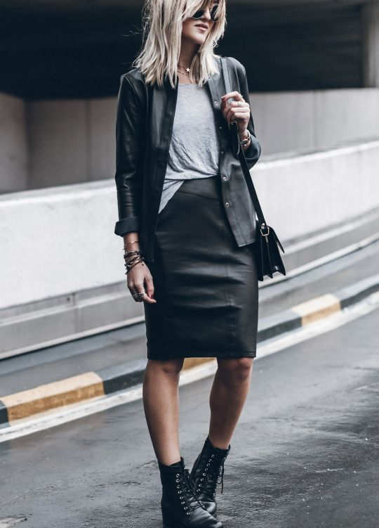 a grey t-shirt, a black leather knee skirt, a black leather shirt, black combat boots and a bag