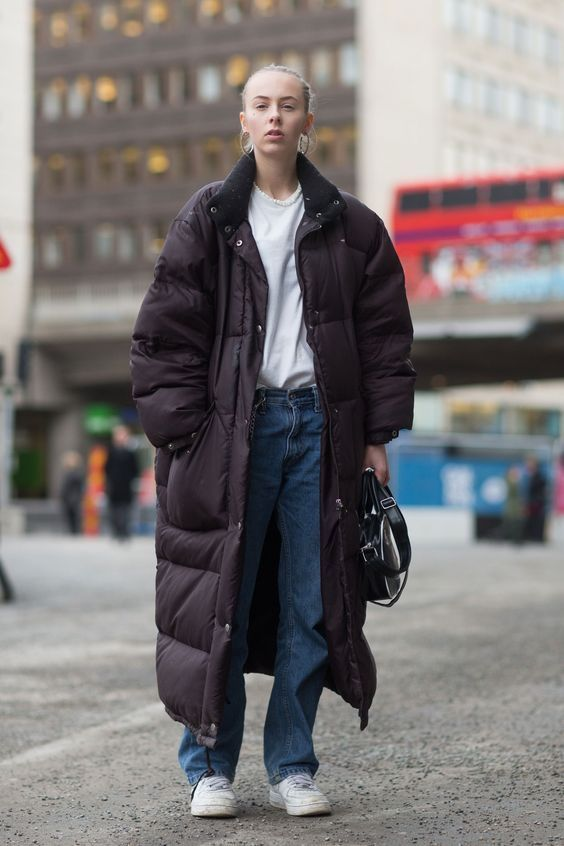 a relaxed outfit with blue jeans, a white tee, white sneakers and an oversized black padded coat