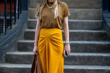 04 a rust-colored tee, an asymmetrical marigold maxi skirt, snake print shoes and a leather bag