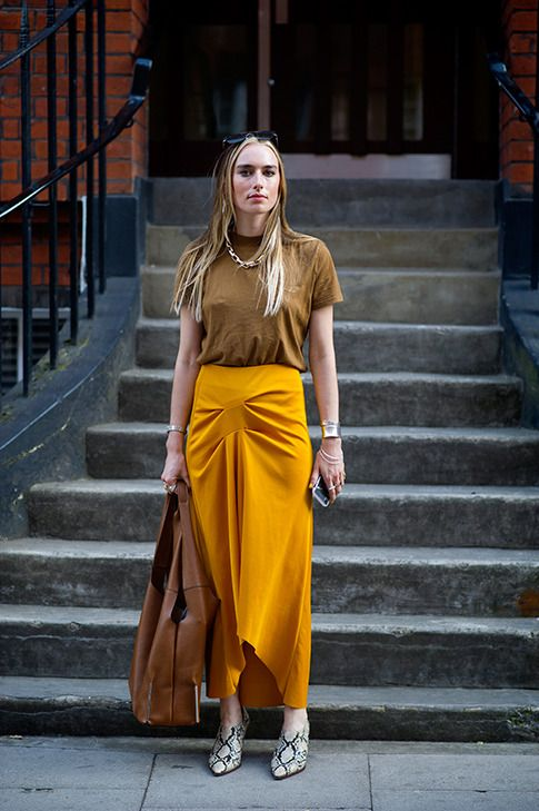 a rust colored tee, an asymmetrical marigold maxi skirt, snake print shoes and a leather bag