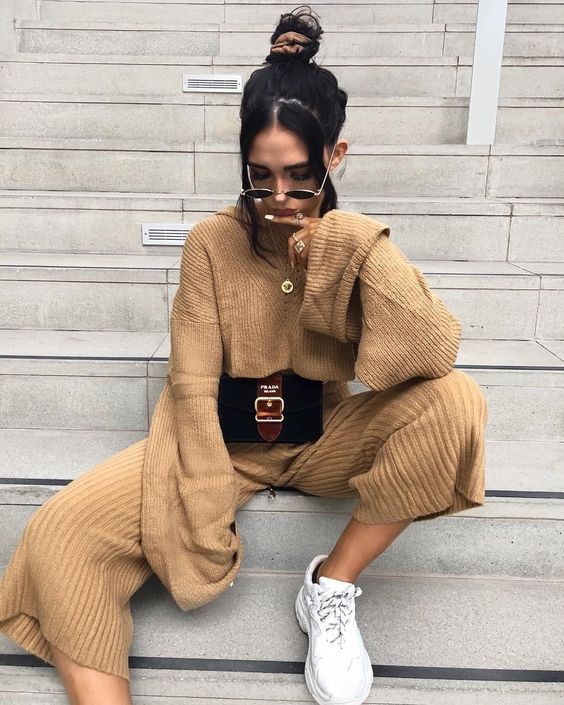 a tan knit suit with culottes and a sweater, white trainers and a belt bag for a comfy winter look