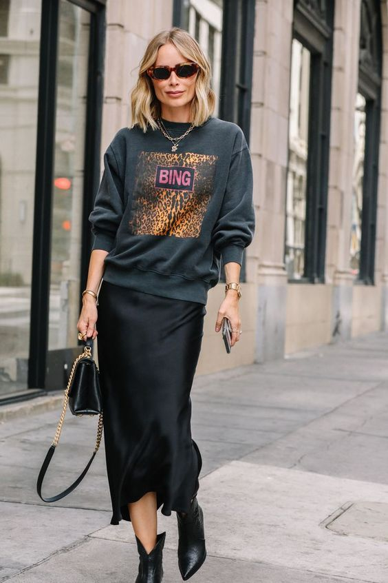 a black midi slip dress, a bold sweatshirt over it, black cowboy boots and a small black bag and layered necklaces