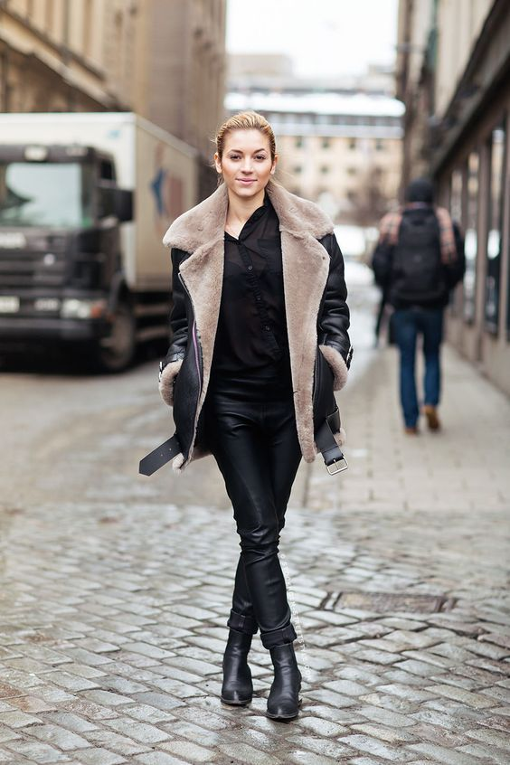 a chic look with a black shirt, black leather pants, black booties and a black and taupe aviator coat