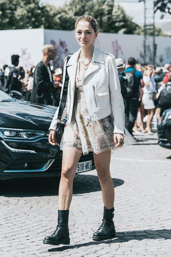 a neutral printed mini dress, a white leather jacket, black combat boots and a black bag