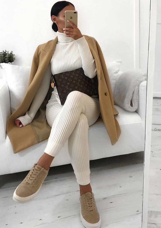 a white knit suit wit pants, a turtleneck top, a camel coat and camel sneakers plus a brown clutch