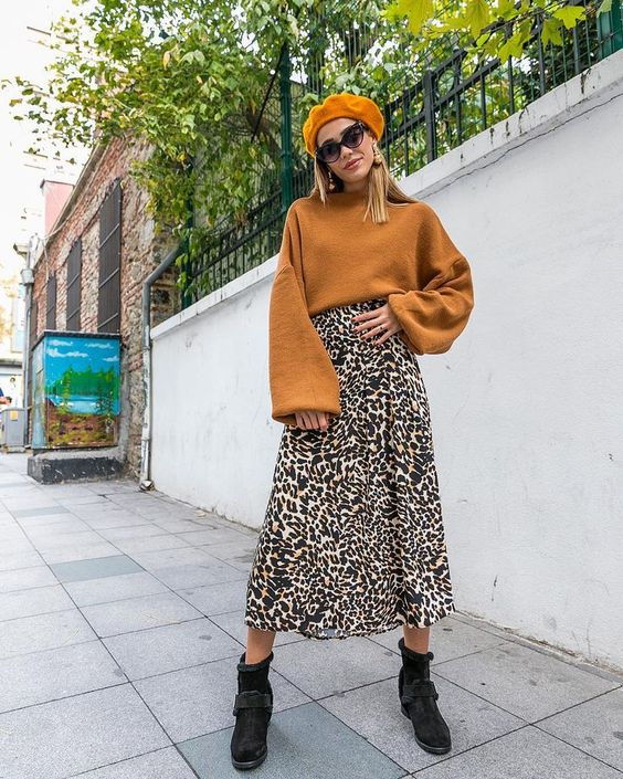 an elegant look with a mustard sweater, a leopard print midi skirt, a mustard beret and black boots